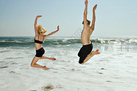 一对夫妇在海滩上与浪共舞图片