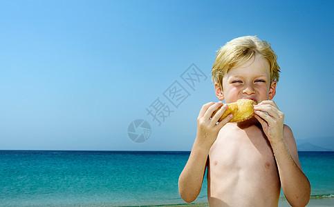 小男孩在海滩上吃甜甜圈图片