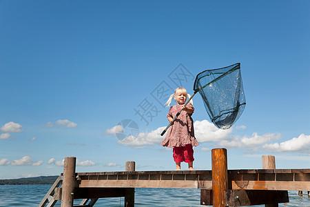 在湖中用网捕鱼的女孩图片
