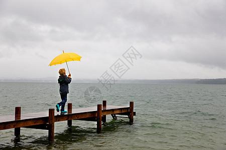 男孩拿着雨伞在木码头上图片