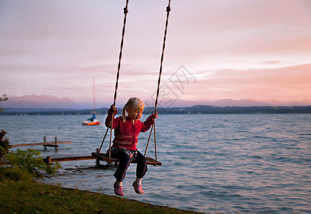 在湖边荡秋千的女孩图片