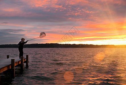 男孩在湖中用网捕鱼图片