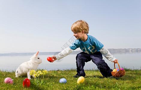 孩子带着小兔子找复活节彩蛋图片