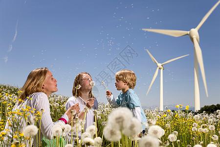 风车前在吹蒲公英的母亲和孩子们图片