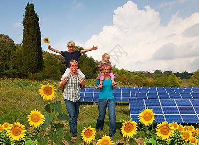 在太阳能电池板傍边的一家人图片