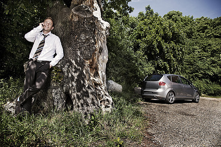 一名男子靠在树上图片