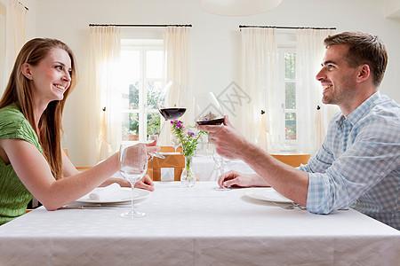 一对夫妇在餐厅用葡萄酒敬酒图片