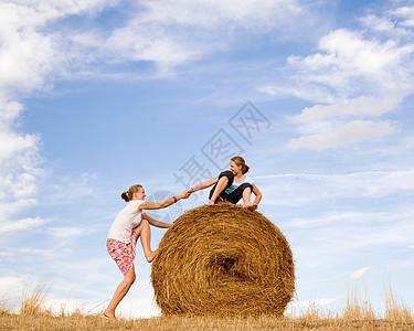 帮女人爬干草捆的女孩图片
