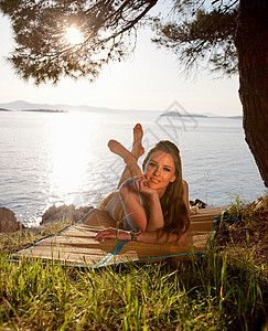 躺在长满草的海滩上的女人图片