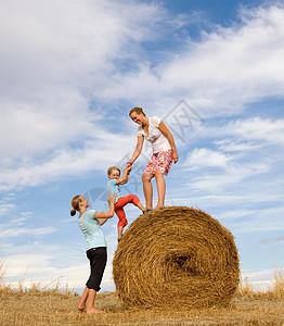 女人帮男孩爬干草捆图片