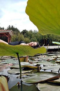 女人躺在池塘边图片