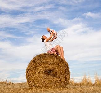 把孩子抱在干草捆上的女人图片