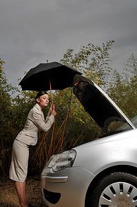 女人看着她的汽车引擎图片