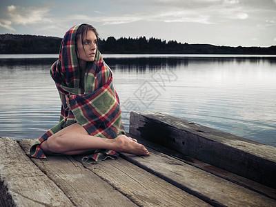 湖边码头上穿着毛毯的女人图片