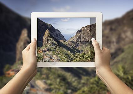 站在西班牙特内里费马萨谷前,手持马萨谷数码平板电脑的年轻女子的双手图片