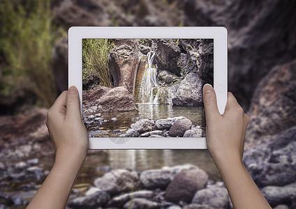 希腊克里特岛撒马利亚峡谷前举着撒马利亚峡谷全景数码平板的年轻女子之手图片