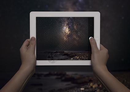 希腊克里特,夜晚,站在银河前的年轻女子手中,手里拿着能看到银河的数字平板电脑图片