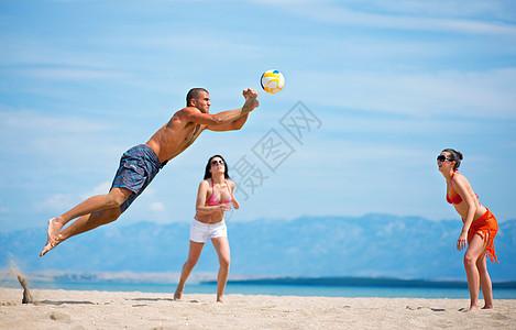 朋友们在沙滩上打排球图片