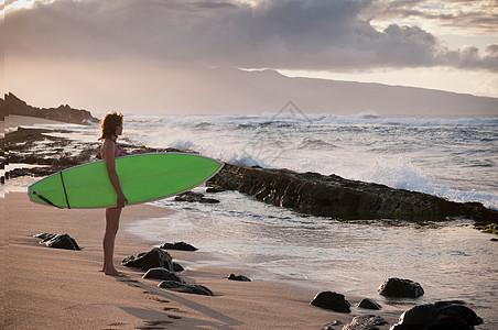 冲浪者在海滩上拿冲浪板图片