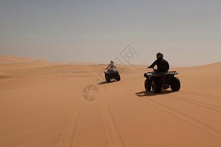 人们在沙地上驾驶四轮车图片
