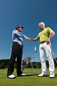 高尔夫球手和球童握手图片