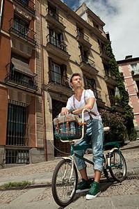 坐在城市街道自行车上的男人图片