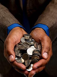 拿着一把硬币的商人图片