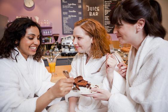 在果汁吧里吃蛋糕的女人图片