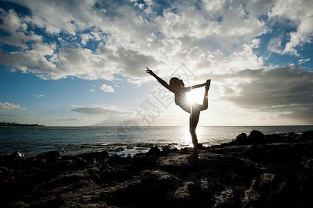 女子练习瑜伽的岩石形成图片