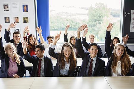 在教室里举起手的青少年学生图片