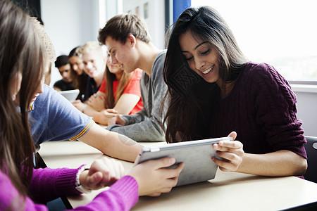 十几岁的女生坐在桌子旁用数码平板电脑图片
