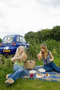 年轻女子在车前吃东西图片