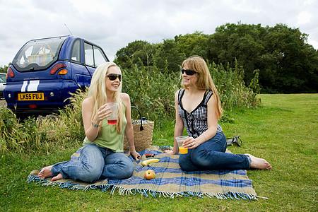 年轻女子在车前喝东西图片