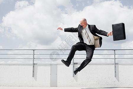 男人拿着公文包跳跃图片