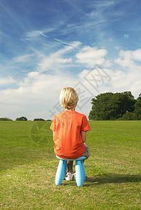 坐在凳子上的金发小男孩图片
