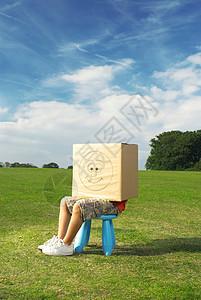 男孩坐在凳子上,盒子放在头上图片