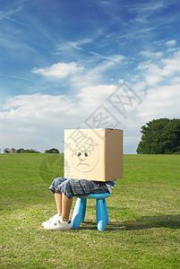 小男孩坐在凳子上,头上戴着盒子图片