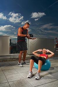 在屋顶上和教练一起锻炼的女人图片