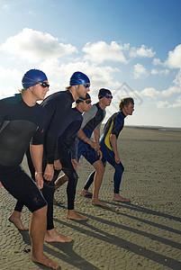 游泳运动员站在海滩上成排图片