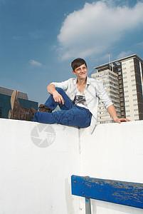 坐在城市屋顶上的男人图片