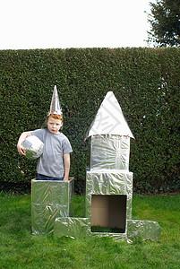 玩纸板宇宙飞船的男孩图片