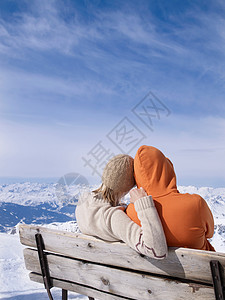 两人坐在长凳上拥抱图片