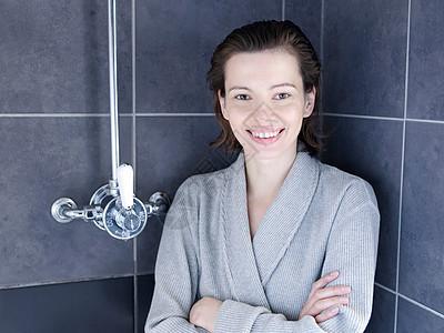 穿着浴袍站在淋浴间的女人图片