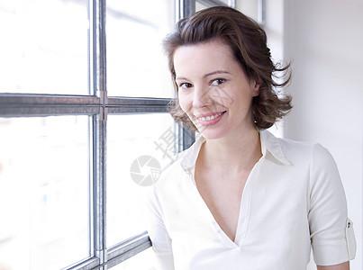 女人靠窗对着镜头微笑图片