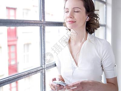 青年女性坐在窗边听音乐图片