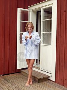 站在门口拿着杯子的女人图片