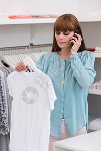女售货员手持T恤的形象图片