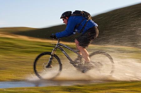 骑山地车的人在水中骑行图片