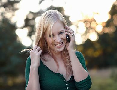 大自然中拿着手机微笑的女人图片