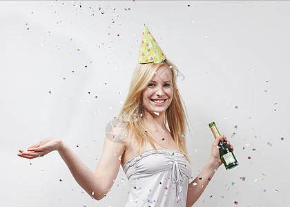 戴着滑稽帽子和五彩纸屑的女人图片